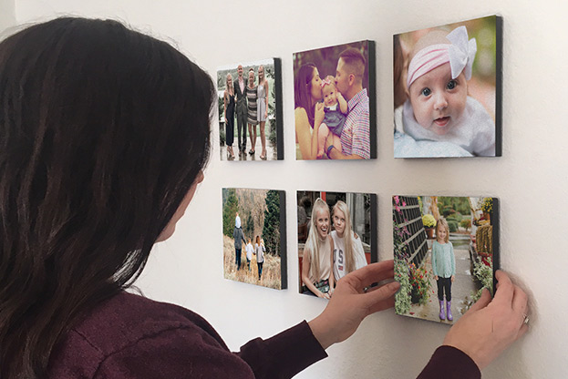 woman applying photo tile decor to wall